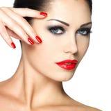 Mooie vrouw met rode spijkers en maniermake-up Royalty-vrije Stock Fotografie