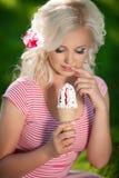 Mooie vrouw met roomijs in openlucht, meisje die icecrea in park eten, de zomervakantie. Vrij blond op aard. gelukkige glimlachend Stock Fotografie