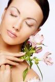 Mooie vrouw met roze bloem Stock Foto's