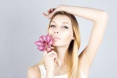 Mooie vrouw met roze bloem en haar opgeheven hand In de was zettende oksel Epilationresultaat royalty-vrije stock foto's