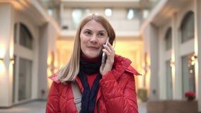 Mooie vrouw met smartphone in wandelgalerij Sprekend door de telefoon, die met haar vrienden communiceren stock video