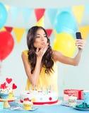 Mooie vrouw met telefoon bij partij, die een kus verzenden Stock Afbeelding