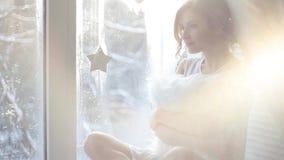 mooie vrouw met verse dagelijkse make-up en romantisch golvend kapsel, die bij de vensterbank zitten Verblindende zonglans stock videobeelden