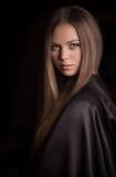 Mooie vrouw met zwarte mantel stock afbeeldingen