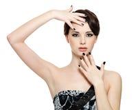 Mooie vrouw met zwarte spijkers Stock Fotografie