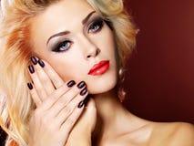 Mooie vrouw met zwarte spijkers en rode lippen stock fotografie