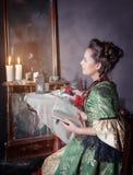 Mooie vrouw in middeleeuwse kleding dichtbij spiegel Royalty-vrije Stock Foto