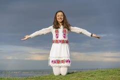 Mooie vrouw in modieuze kleren op de achtergrond van een dramatische hemel Sexy vrouw in nationale kleren stock afbeeldingen