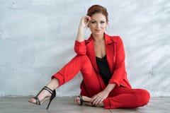 Mooie vrouw in modieuze rode pantsuit in studio Royalty-vrije Stock Foto's