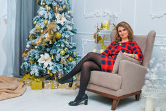 Mooie vrouw netto aan Kerstmisboom, rode kleding Stock Foto
