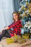 Mooie vrouw netto aan Kerstmisboom, rode kleding Royalty-vrije Stock Foto