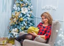 Mooie vrouw netto aan Kerstmisboom, rode kleding Royalty-vrije Stock Afbeeldingen