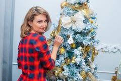 Mooie vrouw netto aan Kerstmisboom, rode kleding Stock Foto's