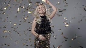 Mooie vrouw onder gouden confettien, langzame motie stock videobeelden