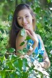 Mooie vrouw onder groene bladeren stock foto