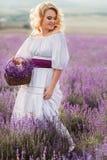 Mooie vrouw op een gebied van tot bloei komende lavendel Royalty-vrije Stock Foto's