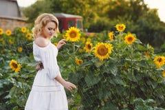 Mooie vrouw op een gebied van zonnebloemen het bloeien Stock Fotografie