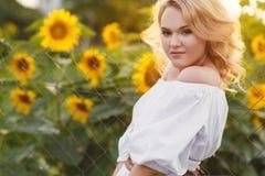 Mooie vrouw op een gebied van zonnebloemen het bloeien Stock Afbeelding