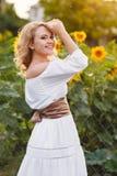Mooie vrouw op een gebied van zonnebloemen het bloeien Royalty-vrije Stock Fotografie