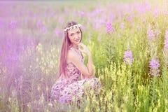 Mooie vrouw op gebied van bloemen Stock Afbeelding