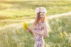 Mooie vrouw op gebied van bloemen Stock Foto