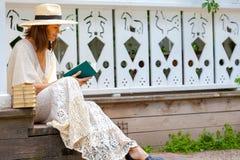 Mooie vrouw op middelbare leeftijd in een strohoed en in een witte kleding stock afbeelding
