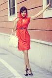 Mooie vrouw op stedelijke achtergrond. Uitstekende stijl Stock Foto