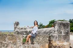 Mooie vrouw op witte kledingszitting alleen bij de muren die de koloniale stad van Cartagena DE Indias omringen stock afbeeldingen