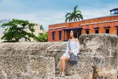 Mooie vrouw op witte kledingszitting alleen bij de muren die de koloniale stad van Cartagena DE Indias omringen royalty-vrije stock afbeelding