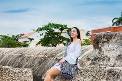 Mooie vrouw op witte kledingszitting alleen bij de muren die de koloniale stad van Cartagena DE Indias omringen stock afbeelding
