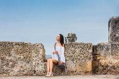 Mooie vrouw op witte kledingszitting alleen bij de muren die de koloniale stad van Cartagena DE Indias omringen royalty-vrije stock afbeeldingen