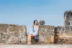 Mooie vrouw op witte kledingszitting alleen bij de muren die de koloniale stad van Cartagena DE Indias omringen stock foto