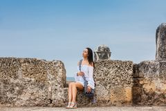 Mooie vrouw op witte kledingszitting alleen bij de muren die de koloniale stad van Cartagena DE Indias omringen royalty-vrije stock fotografie