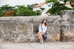 Mooie vrouw op witte kledingszitting alleen bij de muren die de koloniale stad van Cartagena DE Indias omringen royalty-vrije stock foto's