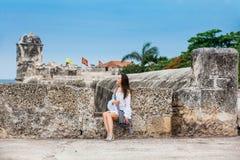 Mooie vrouw op witte kledingszitting alleen bij de muren die de koloniale stad van Cartagena DE Indias omringen stock fotografie