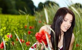Mooie vrouw in papaverbloemen Stock Foto's