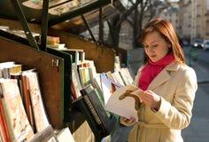 Mooie vrouw in Parijs dat een boek selecteert Stock Afbeeldingen