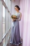 Mooie vrouw in pruimkleding het stellen met een boeket van rozen dichtbij venster Royalty-vrije Stock Afbeeldingen