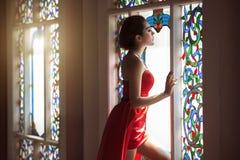 Mooie vrouw in rode kleding Stock Afbeeldingen