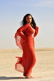 Mooie vrouw in rode kleding in Arabische woestijn. Stock Fotografie