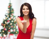 Mooie vrouw in rode kleding die lege hand tonen Stock Foto