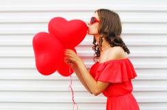 Mooie vrouw in rode kleding het kussen het hartvorm van luchtballons over witte achtergrond Royalty-vrije Stock Afbeelding