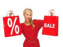 Mooie vrouw in rode kleding met het winkelen zak Stock Afbeeldingen