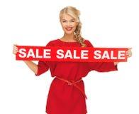Mooie vrouw in rode kleding met verkoopteken Royalty-vrije Stock Afbeeldingen
