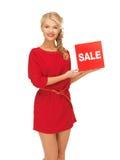 Mooie vrouw in rode kleding met verkoopteken Royalty-vrije Stock Foto's