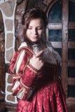 Mooie vrouw in rode kleding in retro barokke stijl Stock Afbeelding