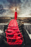 Mooie vrouw in rode lange kleding die zich op een waterval bevinden Royalty-vrije Stock Afbeelding