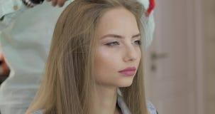 Mooie vrouw in salon Professionele kapper die kammend modelhaar stileren stock video