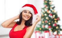 Mooie vrouw in santahoed over Kerstmisboom Royalty-vrije Stock Afbeelding