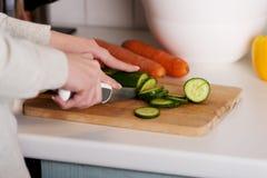 Mooie vrouw in scherpe komkommer op keukenraad. Stock Afbeelding